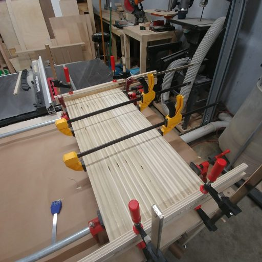 This is how we glued and clamped all of the plywood strips to create the herringbone pattern for the modern sliding barn door.