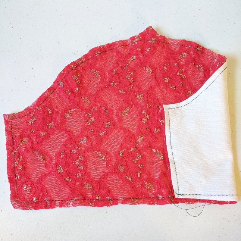 Lace overlay on white fabric basted together