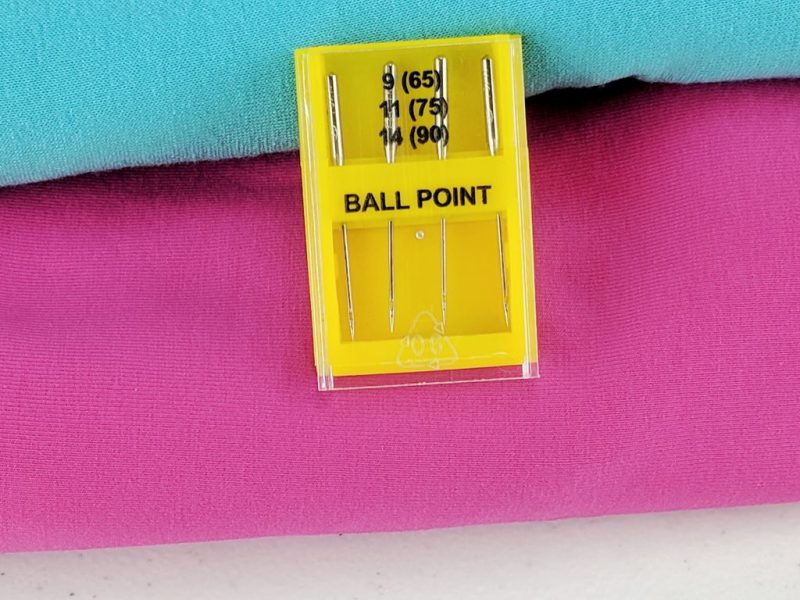 package of ball point needles laid on pink and blue fabric.