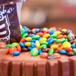 Pour enough M&Ms onto the top of the cake to spread out and fill evenly