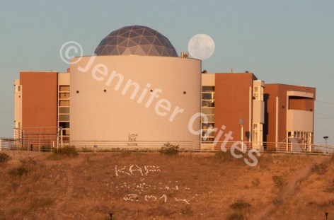 The afternoon moon balances on the edge of a planetarium in Trelew, Argentina.