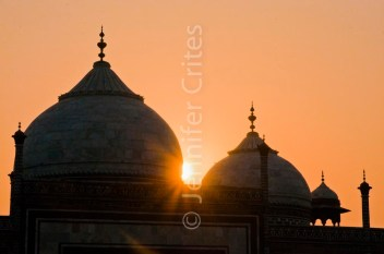 Sun rays from behind domes of the Taj Mahal
