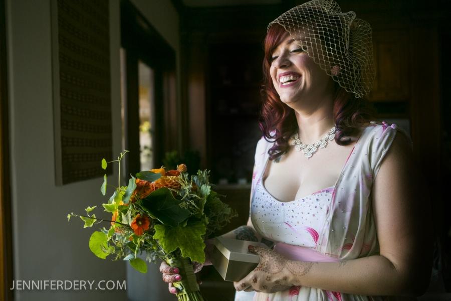 photo of bride with red hair, vintage dress and geranium + nasturtium wedding bouquet
