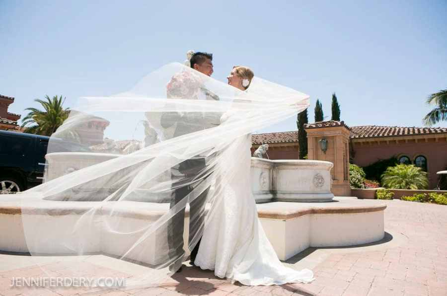 photo of a silk white wedding veil blowing in the wind outside.