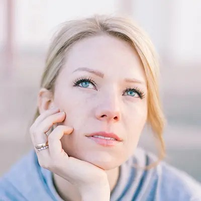 A woman sits looks away from the camera. She has decided to start polyaffirming therapy in Dallas, TX with Rethink Therapy.