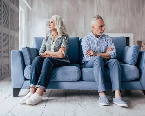 Man and woman sitting with back to each other on couch for discernment counseling in Texas. They are deciding whether or not to get divorced and need a discernment counselor to help with online therapy in Texas from Dallas, TX counselor Jennifer Gay.