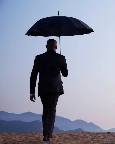 A man walks away holding an umbrella. He is feeling overwhelmed and has decided to start trauma therapy in Dallas, TX with Jennifer Gay, trauma therapists in Dallas, TX at Rethink Therapy. for online therapy in Texas