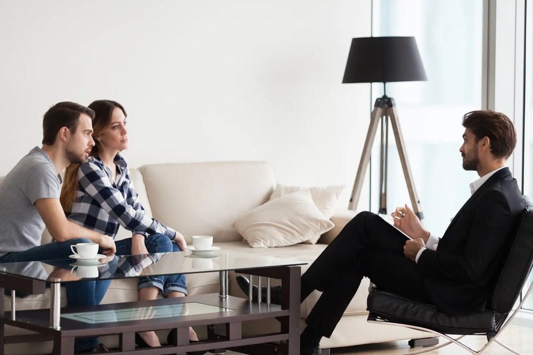 A couple sit in an office for their counselor in University Park, TX. They are going through counseling for affair recovery in Dallas, TX  with Rethink Therapy 75205.