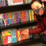 Jennifer gesturing to Sassy Cat Mystery series on the bottom of a bookshelf