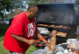 Antone Linton of Harry Q's BBQ places a slab of ribs on the grill.