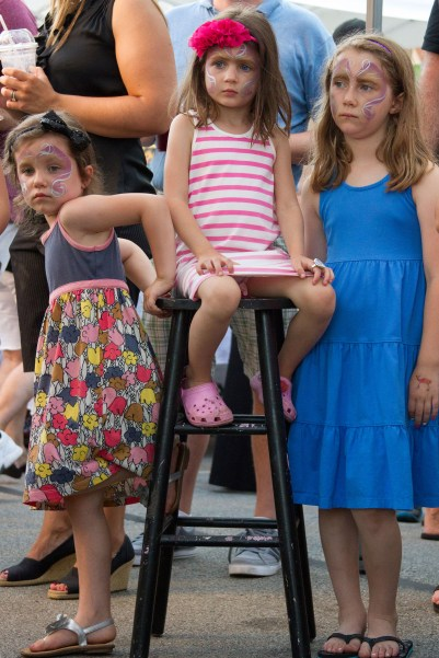 Elia Bursua, left, Erin Defauw, center, and Maura Defauw, right, wait for their face painting to be completed.