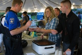 Jennifer Gallion grabs a sample of the North Riverside Police Department's entry during the North Riverside Autumn Fest and Chili Cook-Off on Sept. 18.