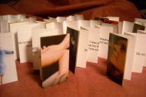 """Correspondence Books, 2014. ¾"""" x 2""""; Artist's book series. Cardboard, paper. For this series, I excerpted single sentences from letters, emails, Facebook posts, and feedback on my writing, received from family and friends. Each small accordion book contains one of these sentences, illustrated with cover art cut from various magazines."""