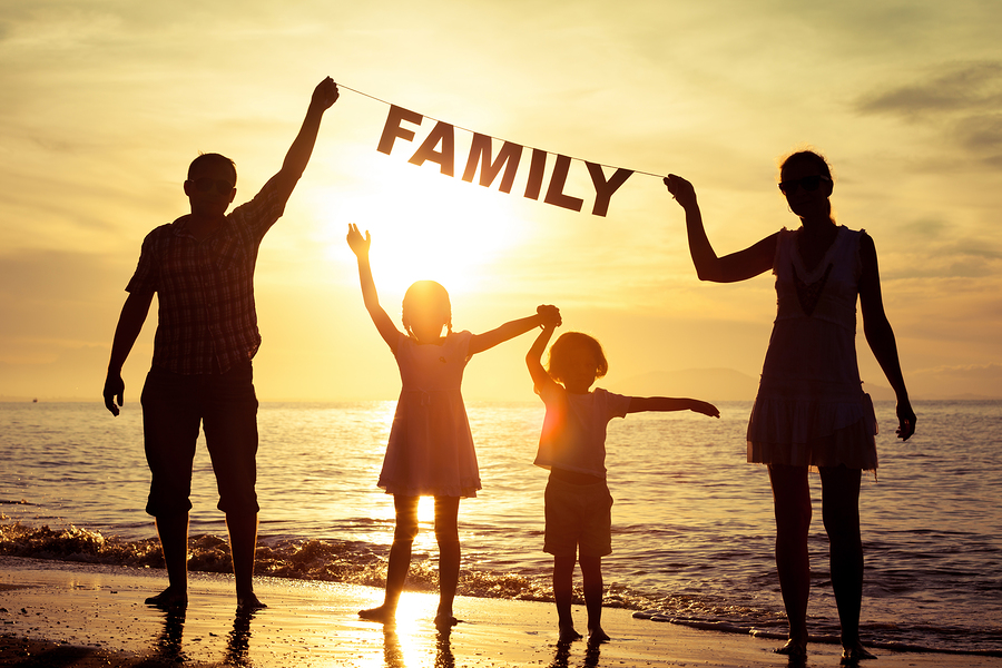 Happy Family Standing On The Beach