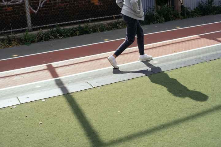 crop child walking fast on stadium