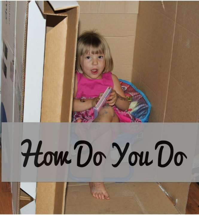 toddler sitting in a box acting like it is her house waiting for someone to come over so she can work on her social skills