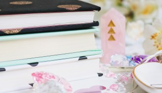 Close up photo of 3 notebooks with a rose quartz crystal in the background
