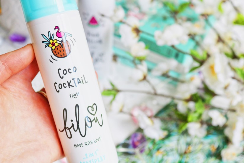 Close up photo of the bilou Coco Cocktail Bodyspray with white flowers blurred in the background