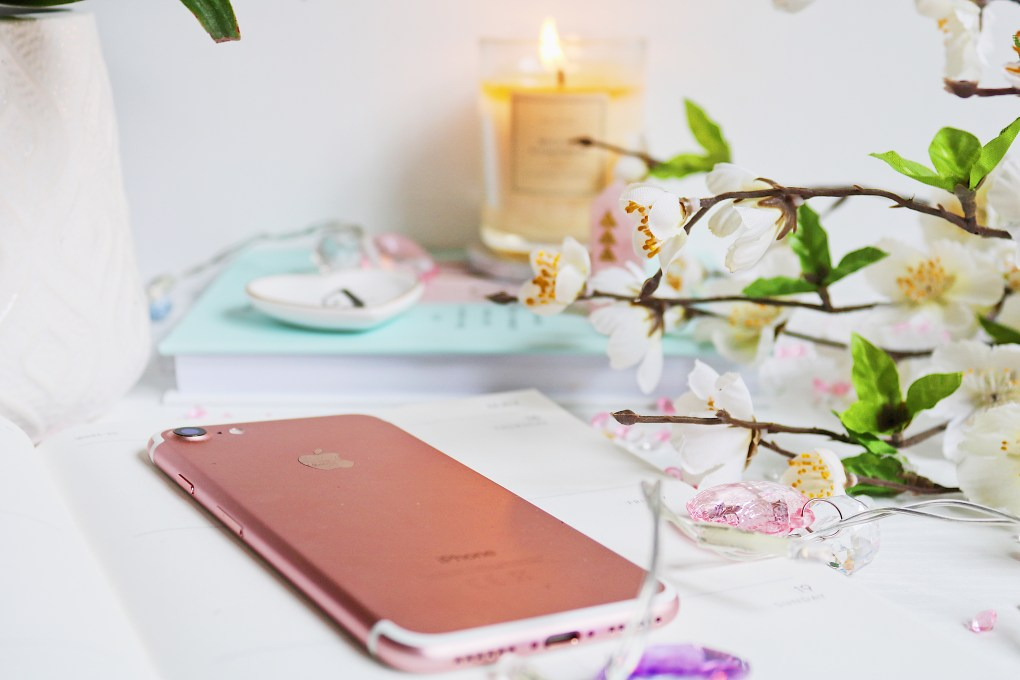 Close up photo of a rose gold iPhone with a notebook and candle in the background