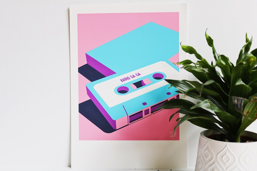 "Father's Day Gift Guide: An image of a print of a illustrated cassette tape with the song ""Radio Ga Ga"" written on it. A small plant in a white pot sits next to it."