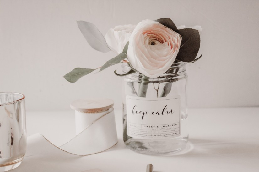 A clear jar on a desk with light pink roses in. The jar has a label that says 'keep calm'