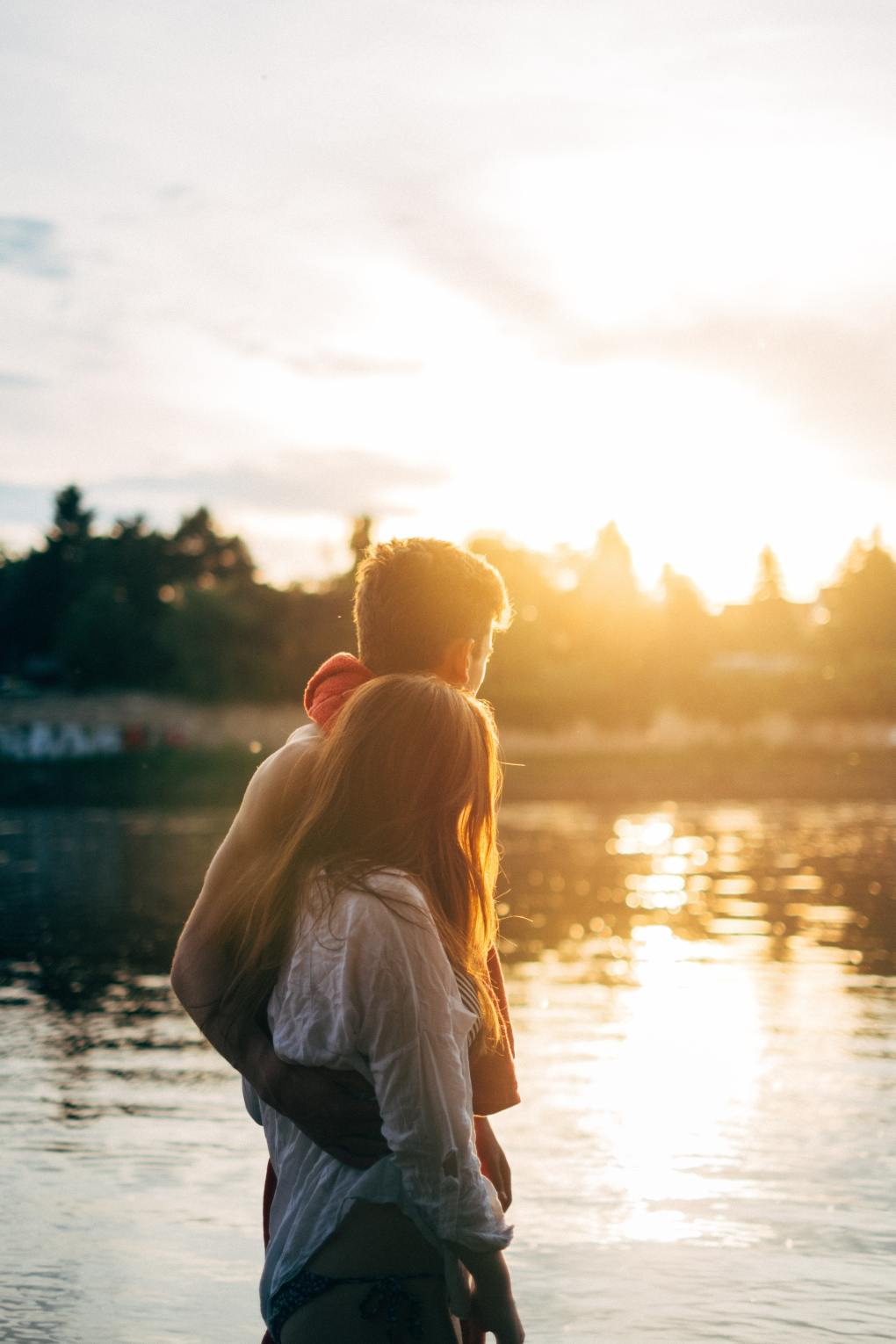 Couple Walking Arm in Arm Beside a Lake At Sunset