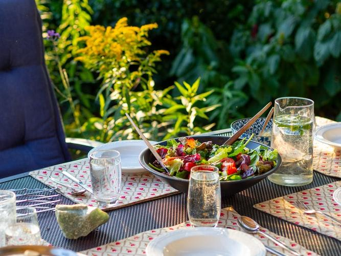 A colorful salad sits in a black serving dish on top of an outdoor table, surrounded by glasses of water and decorative placemats.