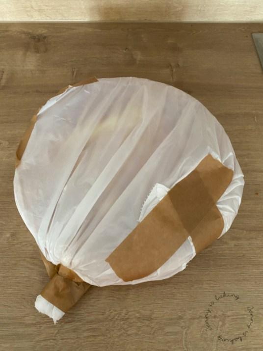 Ein Tortenboden wird gut zum Einfrieren eingepackt