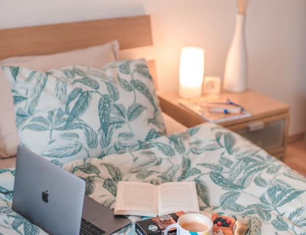 blue bed with laptop and coffee mug
