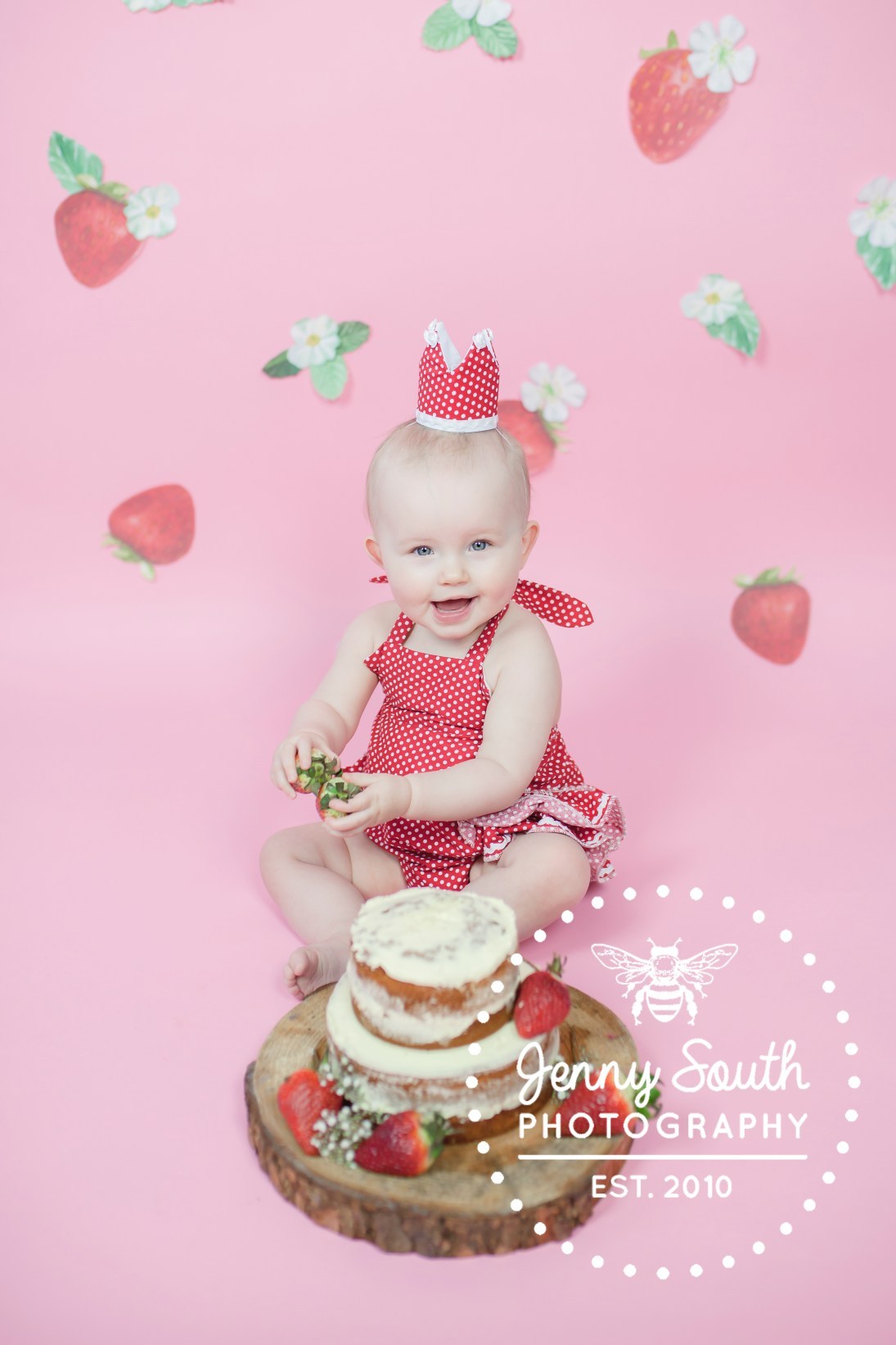 Baby girl enjoying her strawberry themed cake smash
