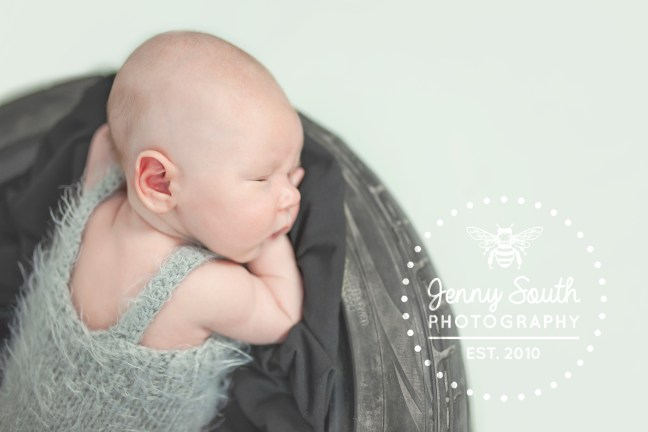 Little baby boy asleep on a tyre against a grey background