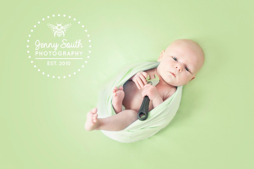 Newborn Baby on a green background holding a spanner