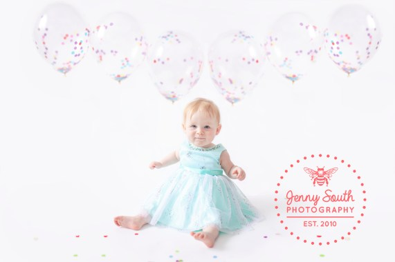 Baby Girl in a green dress with confetti balloons floating behind her, all ready for her cake smash session in our Plymouth Studio