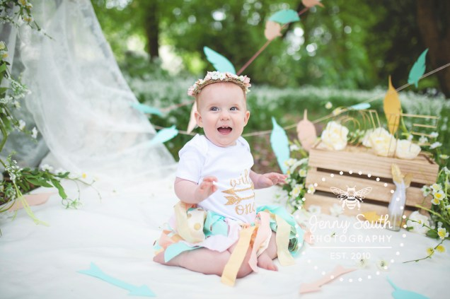 Baby Girl laughs whilst wearing a rag tutu surrounded by a themed wild one set for her cake smash session