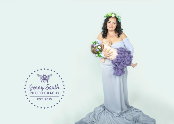 Breastfeeding Mother wears purple flowing dress whilst nursing her daughter. Both wear matching Flower Crowns