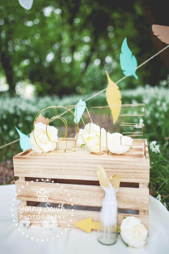 Gold wire letters sit on top of a wooden box adorned with wild one inspired props for an outdoor cake smash session in Plymouth