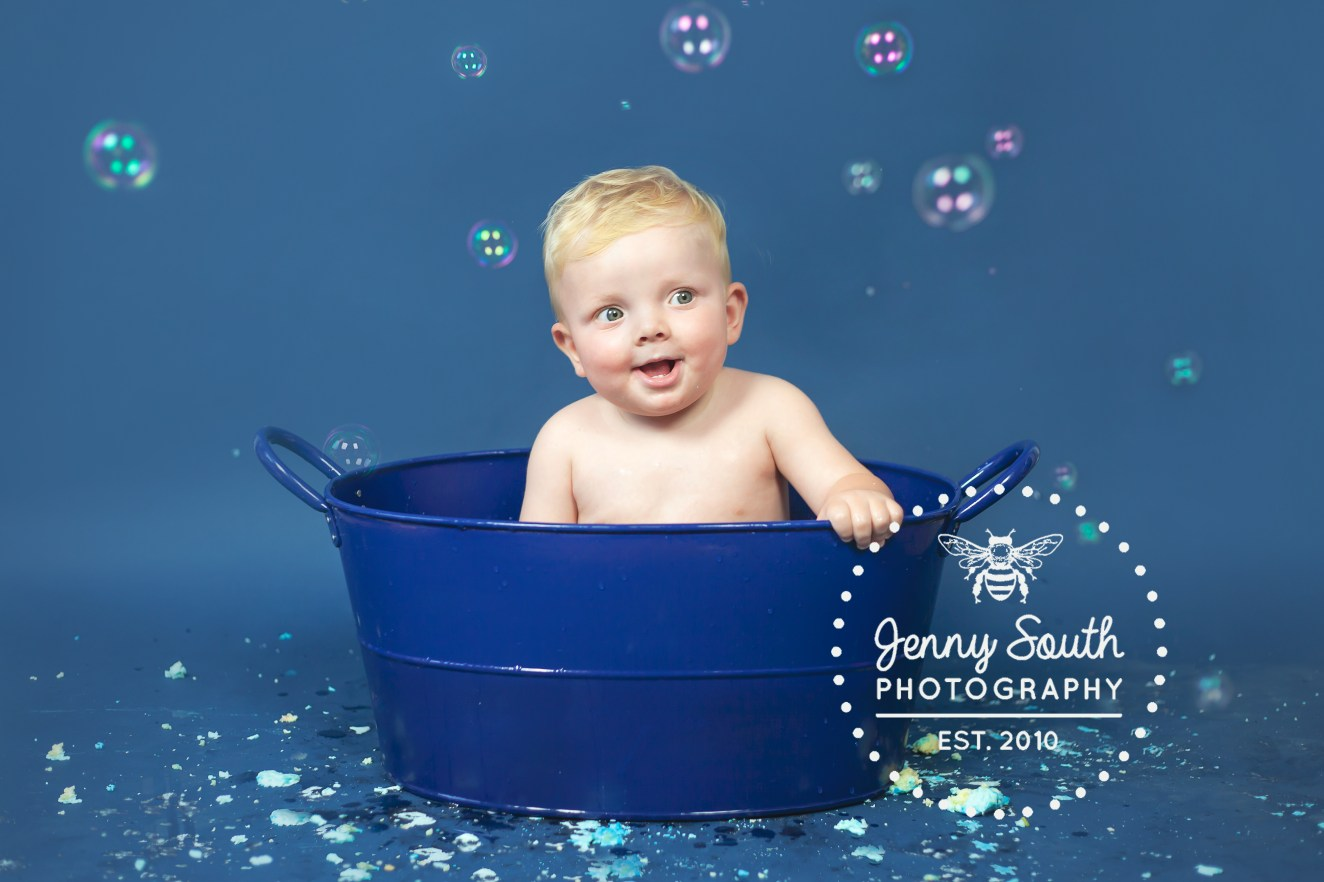 Baby giggles in blue bath tub surrounded by bubbles after his cake smash session in Plymouth