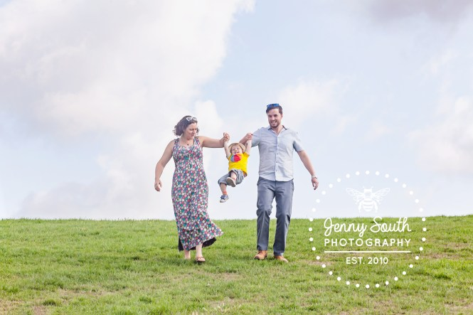 A mother and father swing their son in the air during their family photo session at Devils point in Plymouth