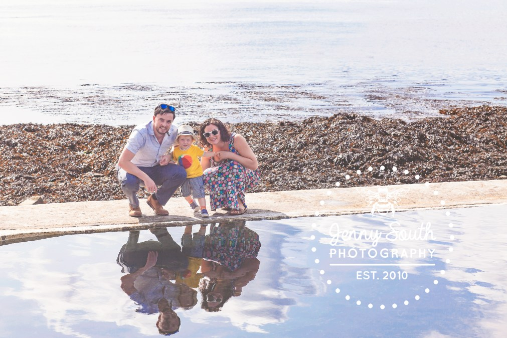 A family take a moment to watch their reflection in a sea water polo