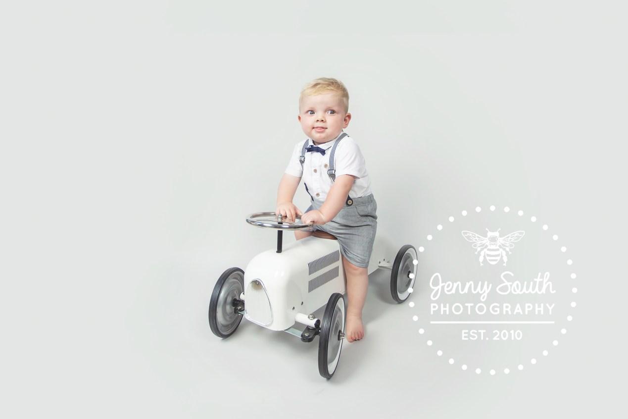 Little boy sits on vintage toy car against a grey background for a studio portrait