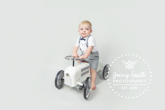 Little boy sits on vintage toy car against a grey background for a studio portrait