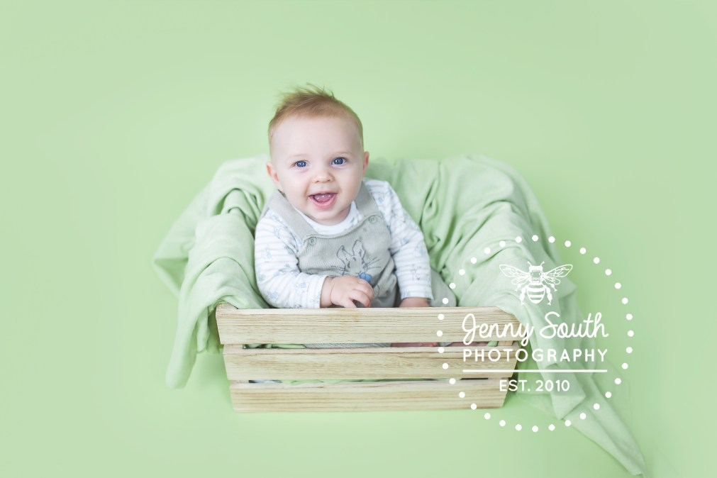 portrait of a baby boy against a green seamless backdrop sitting in a wooden creat