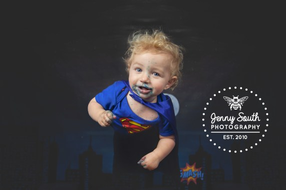Baby dressed as superman flies through the air over a silhouetted city scape