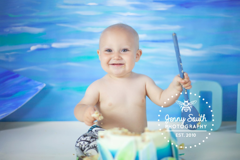A baby boy smiles whilst smashing his cake on his first birthday photography shoot