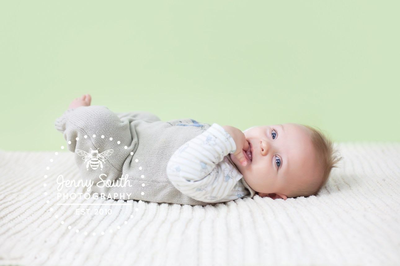 Baby boy lies upon cream cable knit blanket and smiles sweetly.