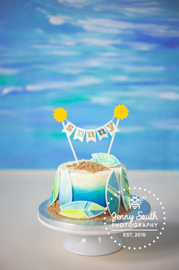 Surfing themed cake with a beautifully designed cake topper with sun, and the name sunny written on. as part of a cake smash session at Jenny South Photography Studio