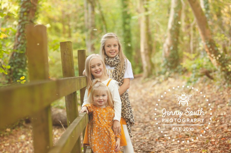 Three sisters smile sweetly in the autumn sunshine during a walk in the woods