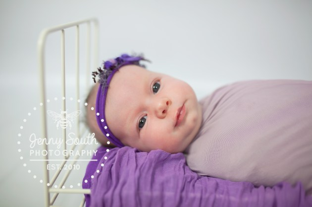 Newborn Baby Smiles sweetly during her session. She lies on a tiny bed decorated with lilacs and purples.