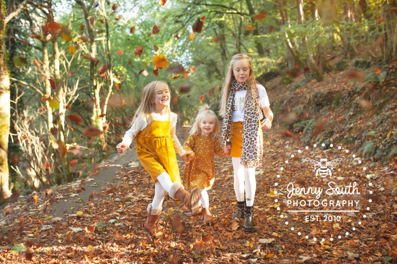 These three sister happily kick and frolic in the autumn leaves of a plymouth woodland