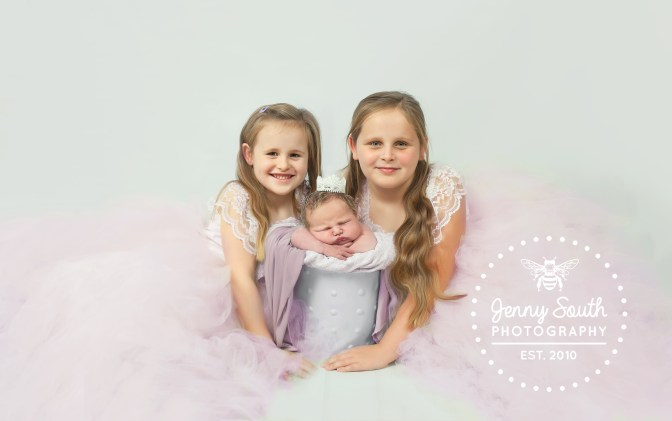 big sisters pose with their newborn baby sister during a family photo shoot in plymouth